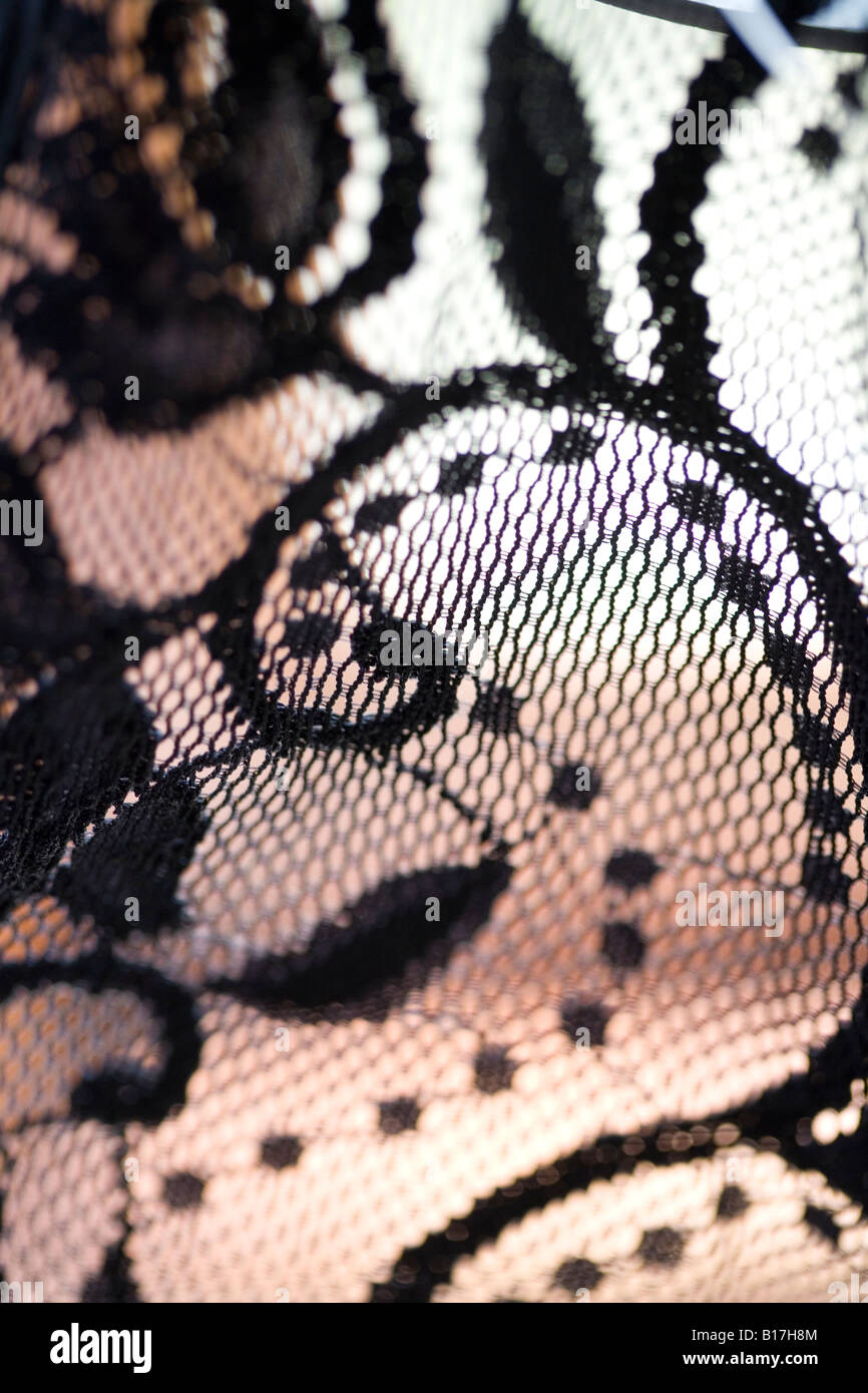 black lace closeup with paisley pattern on a flesh coloured background - Stock Image