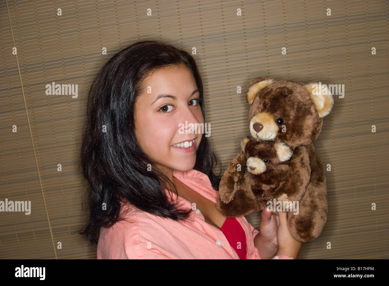 Teen girl holding a pair of stuffed animals Model Released - Stock Image