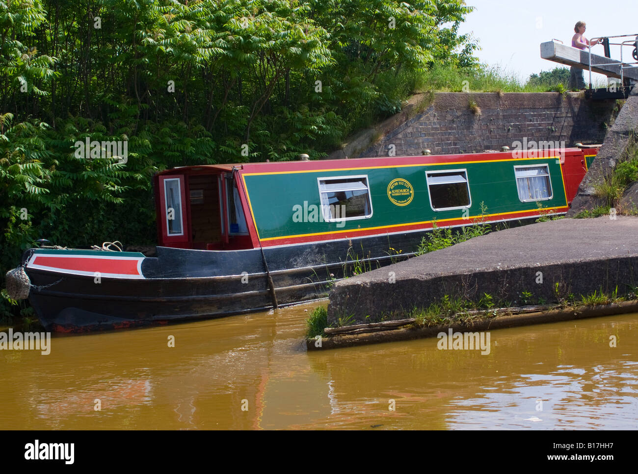 A Narrow Boat Leaving a Lock on the Trent and Mersey Canal near Rode Heath Cheshire England United Kingdom - Stock Image