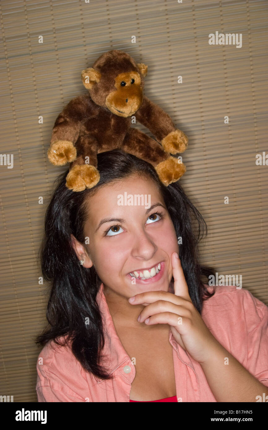 Teen girl with a stuffed animal sitting on her head Model Released - Stock Image