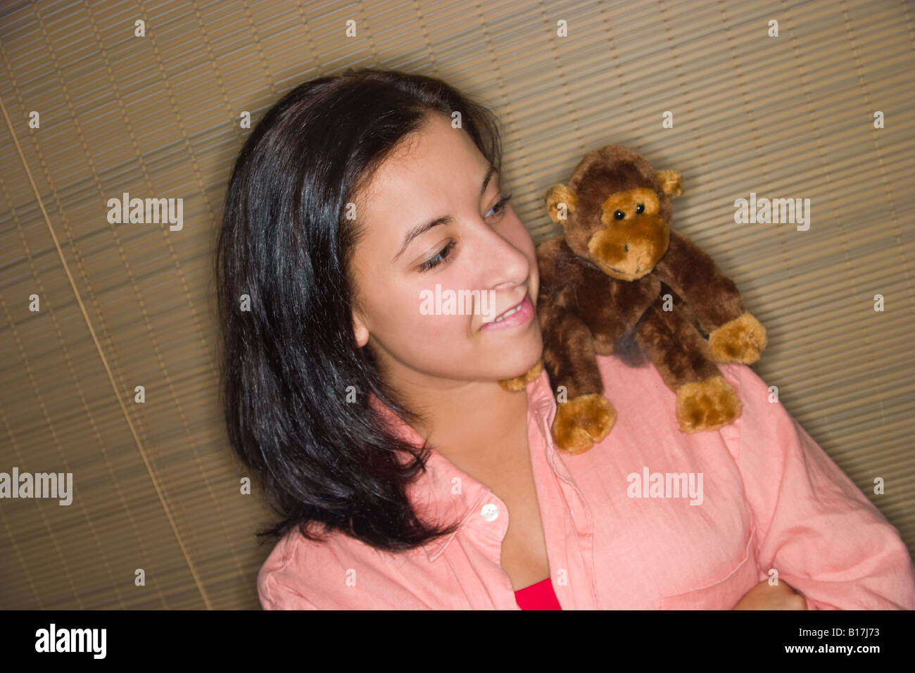 Teen girl with a stuffed animal sitting on her shoulder Model Released - Stock Image