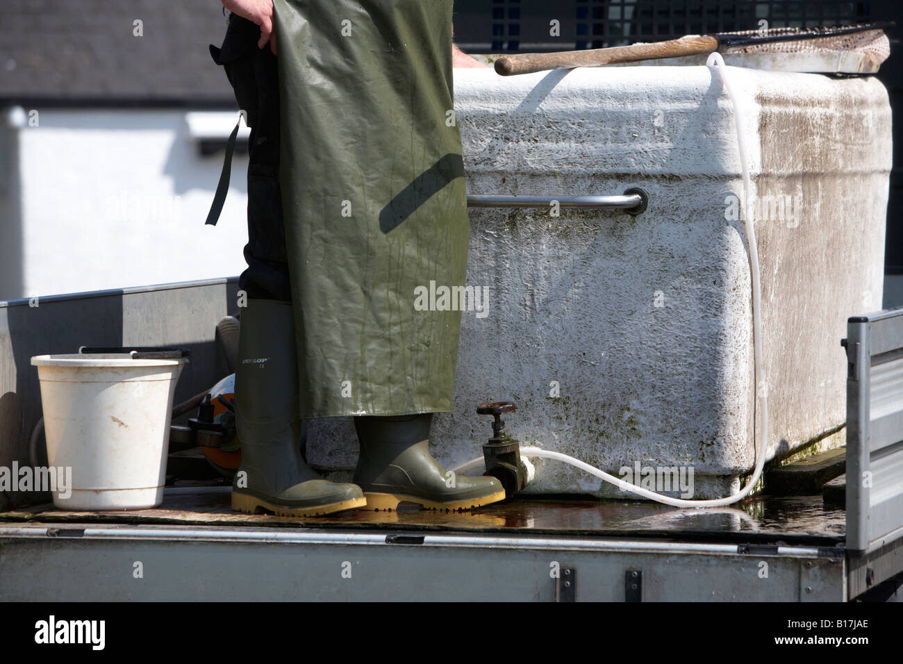 man wearing plastic apron standing beside tank mounted on the back of a van to restock a game fishery county down - Stock Image