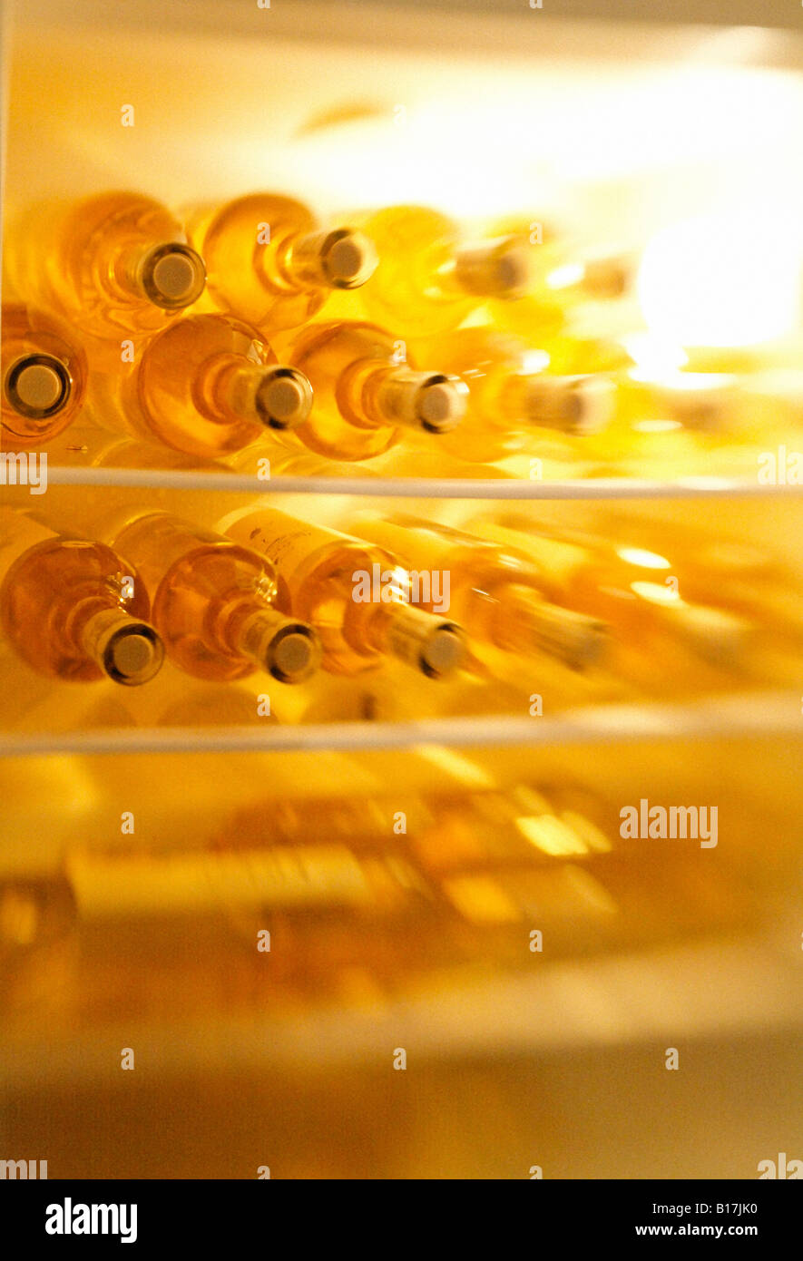 Bottles of white wine in a fridge, blurred - Stock Image