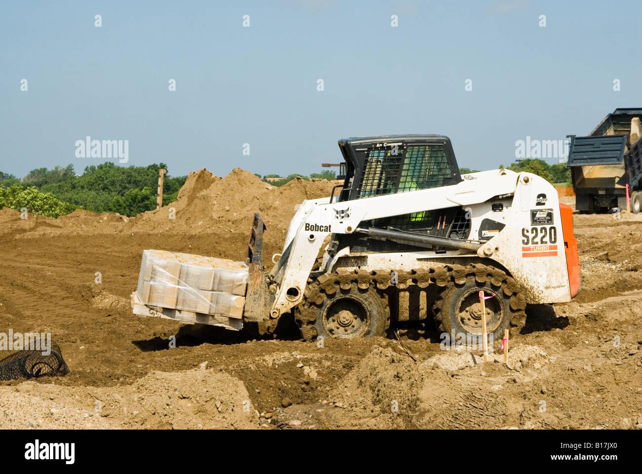 a bobcat skid loader at work on a consturction site Stock