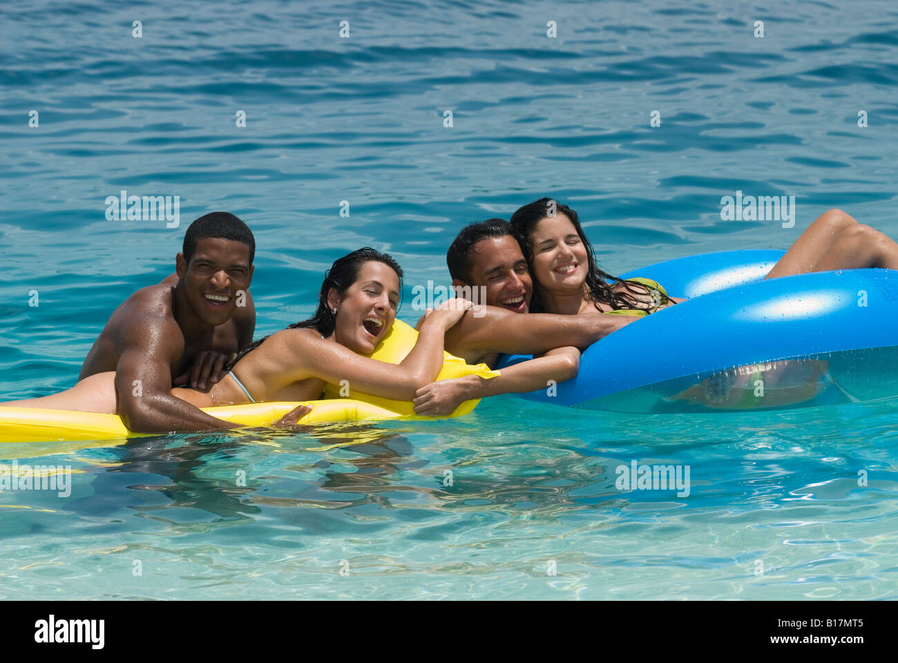 Multi-ethnic friends on floats in water Stock Photo