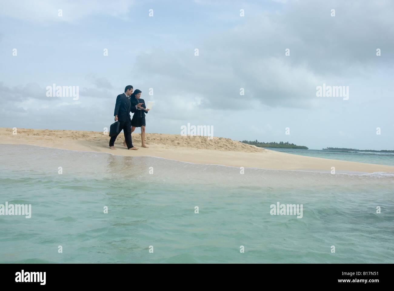Hispanic businesspeople walking on beach Stock Photo