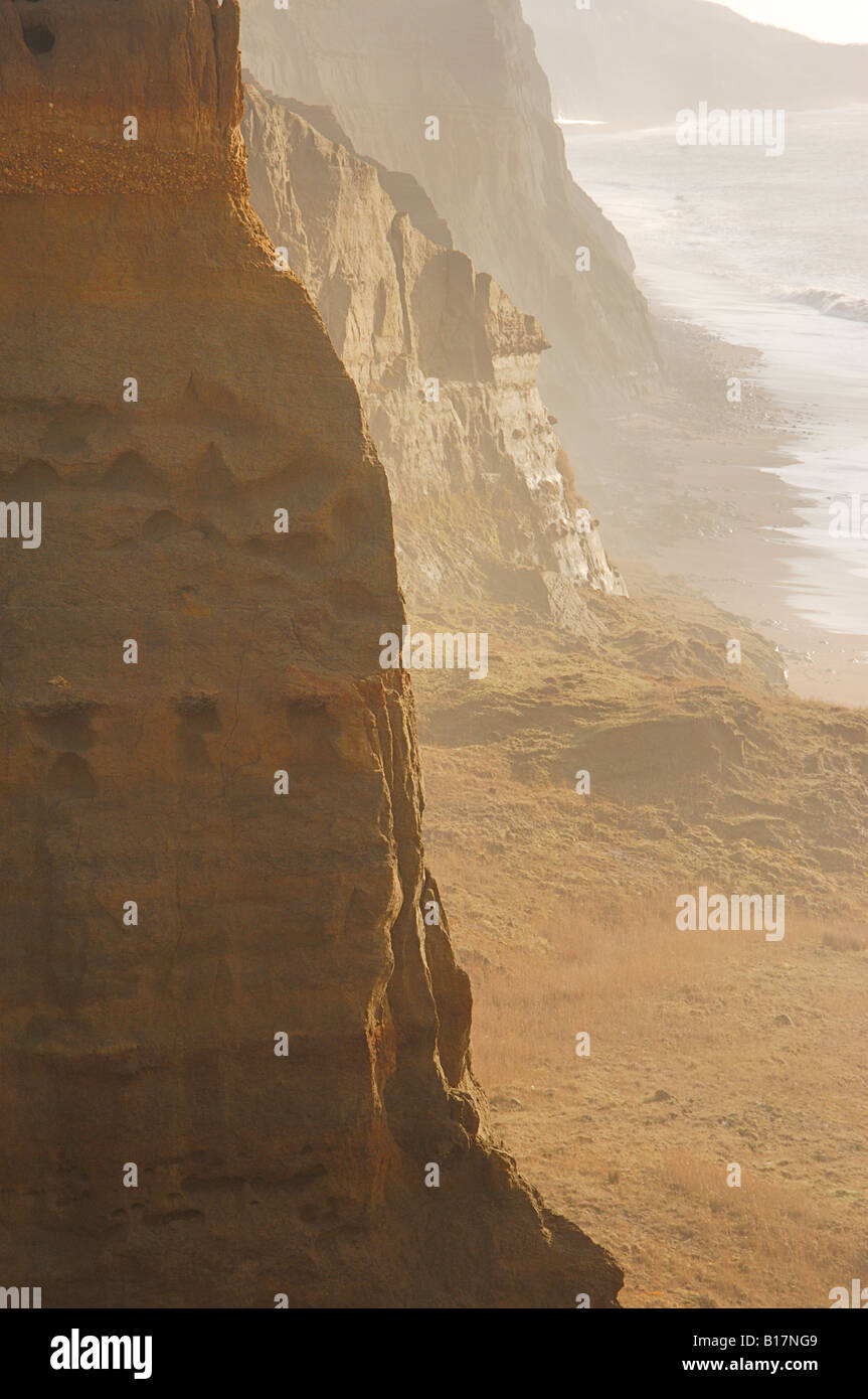 Whale chine in sun and light mist, showing staggered and dramatic cliffs. - Stock Image