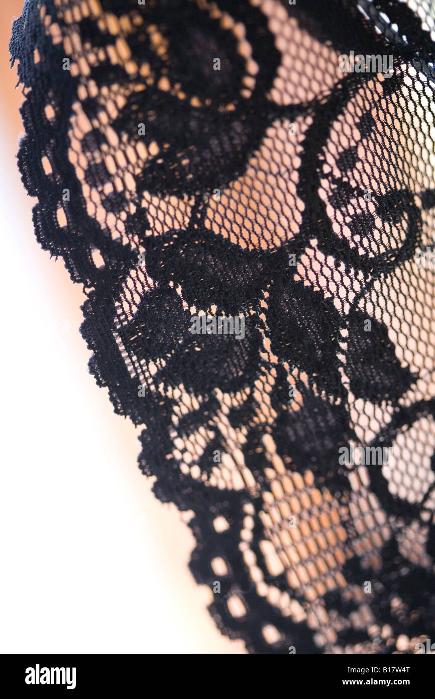 black lace with frilled scalloped edging on a flesh, pale background - Stock Image