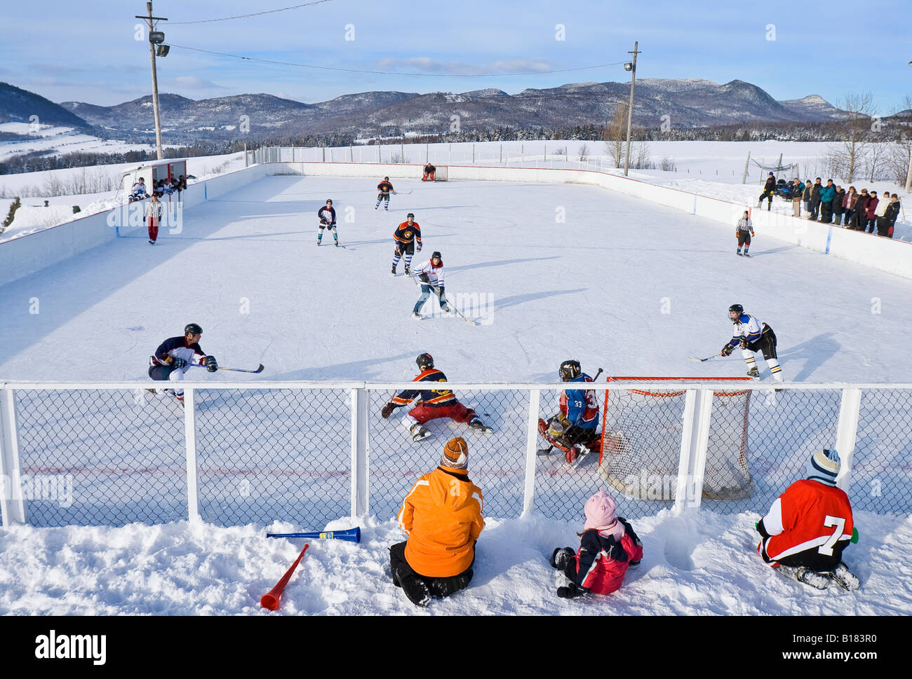 Hockey game played on a village outdoor rink on a pleasent saturday afternoon, Les Éboulements, Québec, - Stock Image