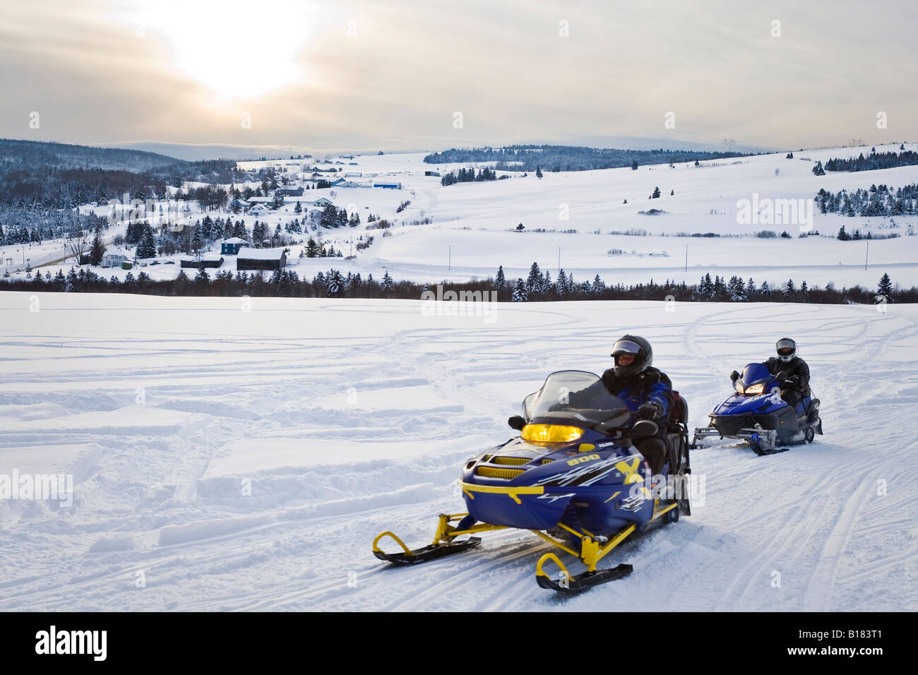 Snowmobilers travelling through Charlevoix's back country, Rang Sainte-Marie, Les Éboulements, Québec, - Stock Image