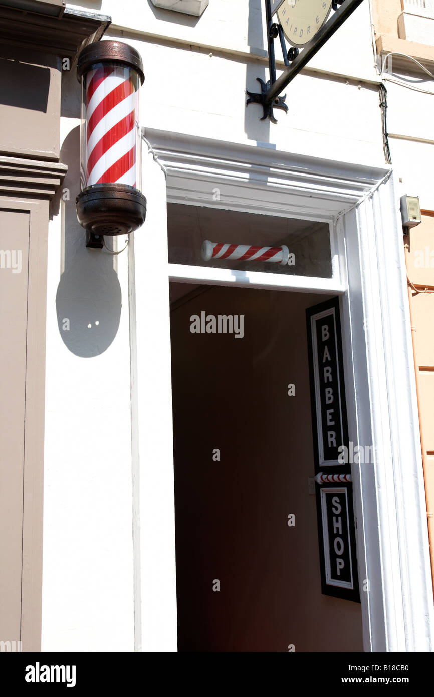 barber shop with traditional striped pole outside in enniskillen county fermanagh - Stock Image
