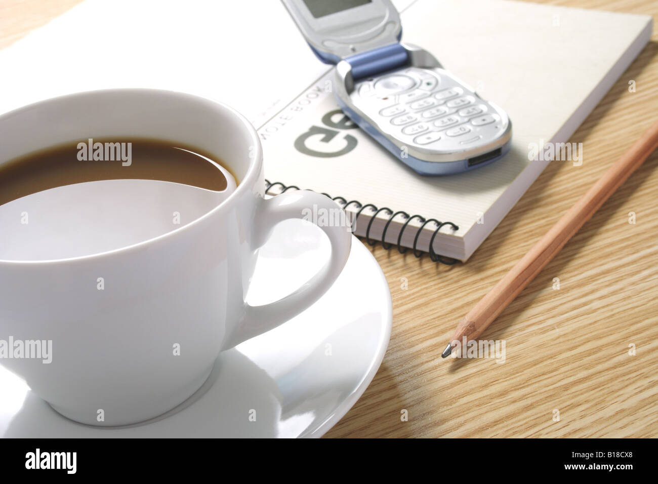 Coffee pencil cellphone and notebook on table Stock Photo