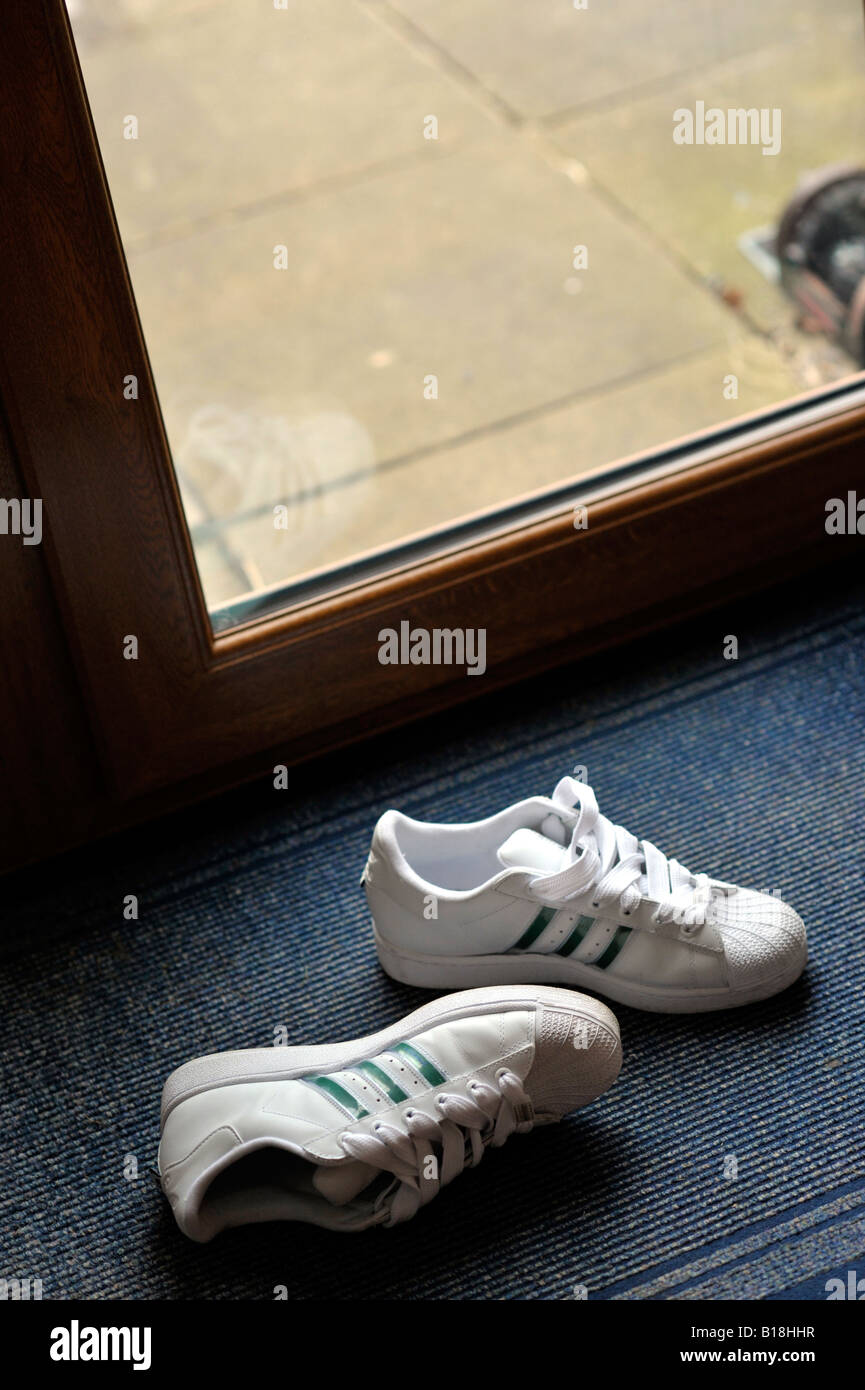 pair of white sports training shoes disgarded on back door mat - Stock Image