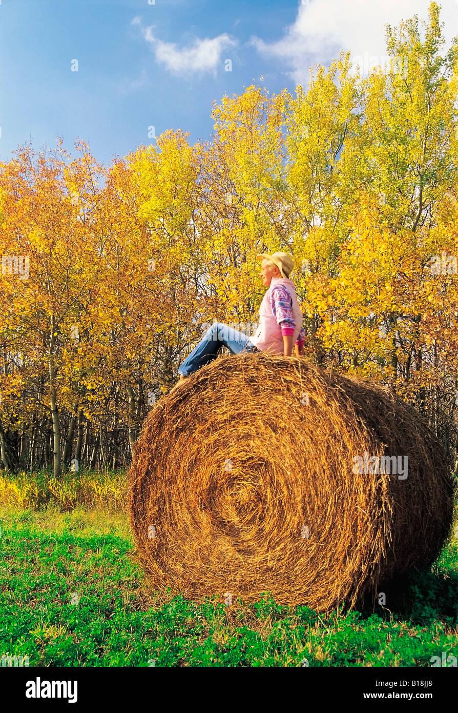 17 year old girl on alfalfa roll, near Winnipeg, Manitoba, Canada - Stock Image