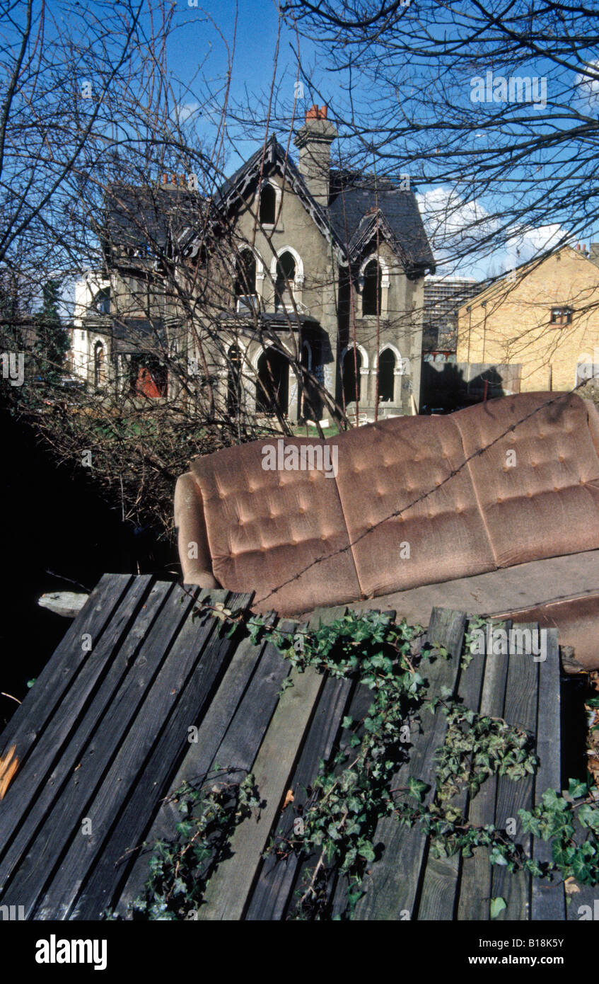 Large derelict Victorian house in Dulwich London SE22 with old furniture and refuse dumped in garden England UK - Stock Image