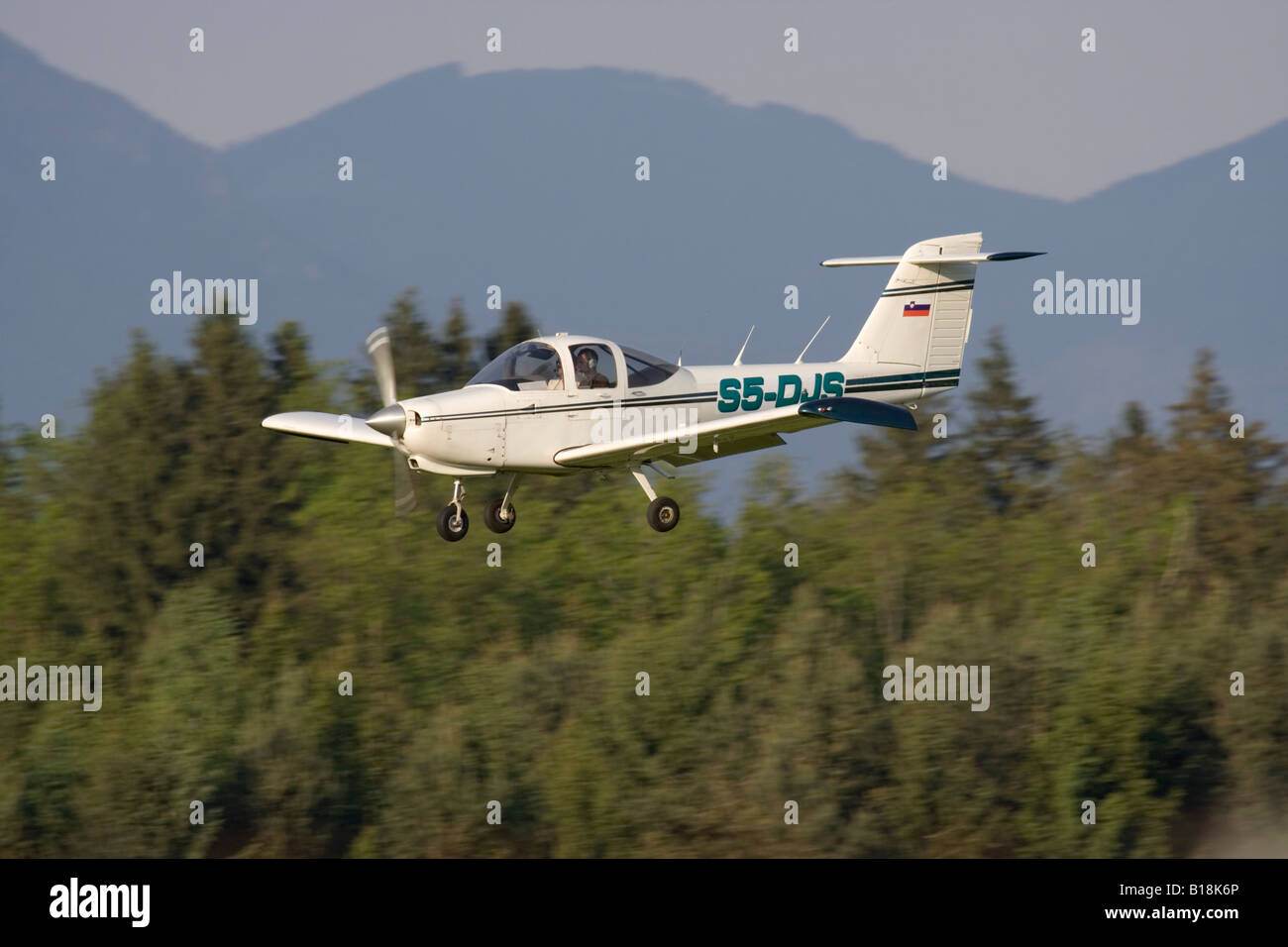 Piper PA-38 Tomahawk single engine light plane landing at Ljubljana Airport - Stock Image