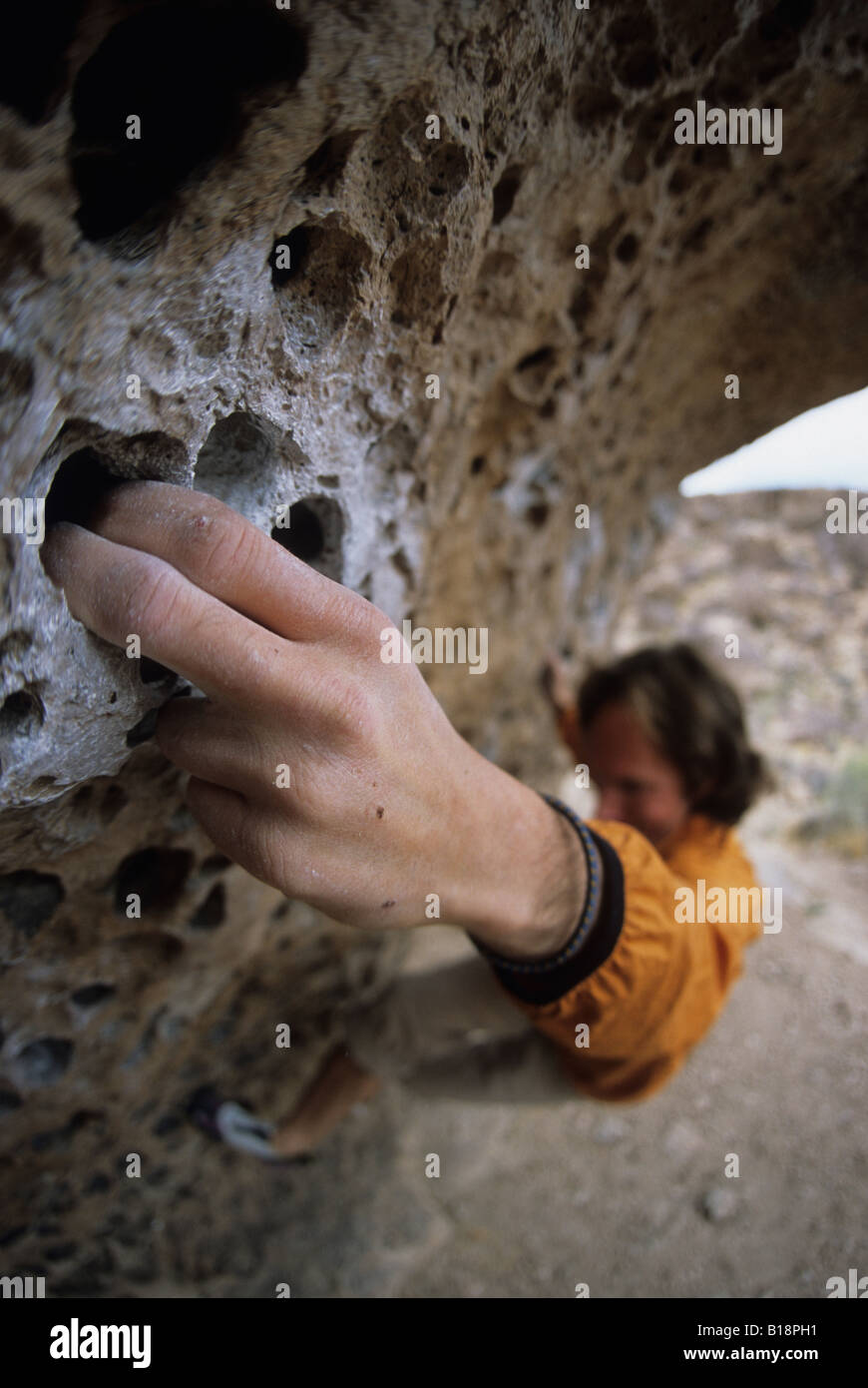 A climbers gripping on to the nice finger pockets on Hand to Hand Combat, v7, Happy Boulders, Bishops, California, - Stock Image