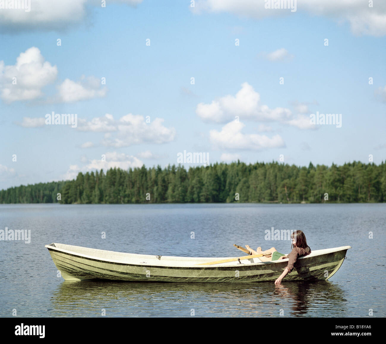Rear view of a woman sitting in a rowboat Finland - Stock Image