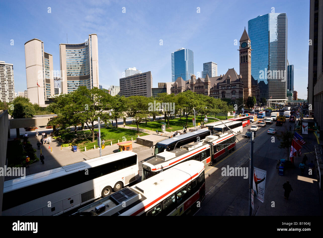 Tourist buses and TTC streetcars on Queen Street in front of both New and Old City Halls, Toronto, Ontario, Canada. - Stock Image