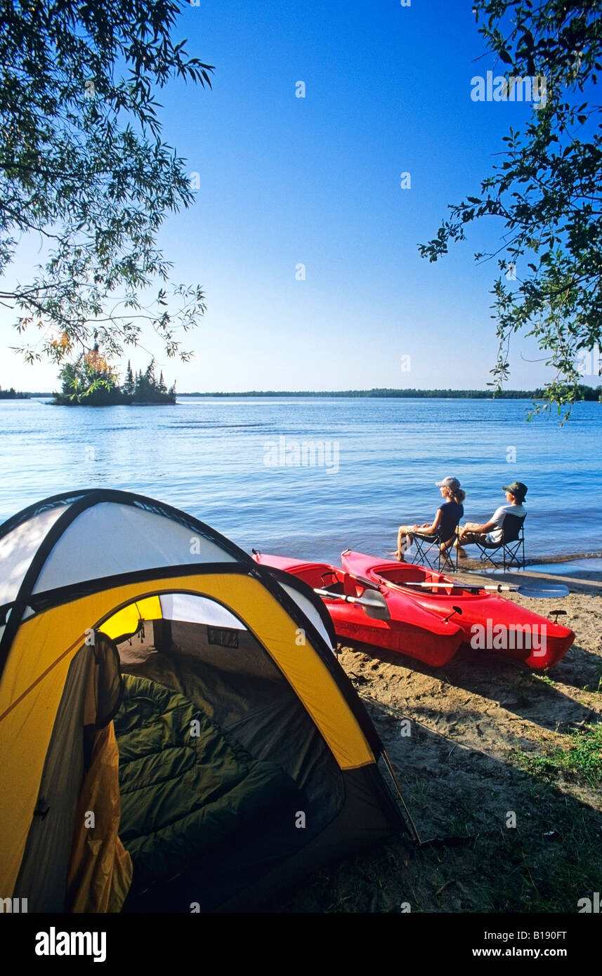 Couple relaxing at Otter Falls campground, Whiteshell