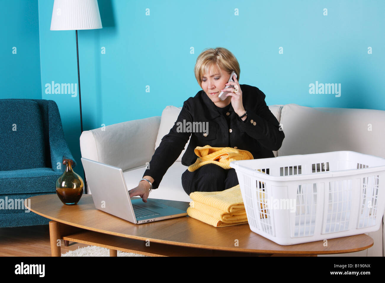 Woman on the phone, working on her laptop and folding laundry - Stock Image