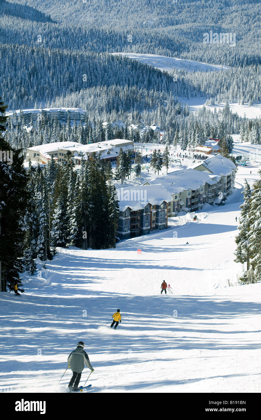 Skiers negotiate Linto's Loop, Slopeside accomodations and daylodge in background at Mt. Washington.  Courtenay, - Stock Image