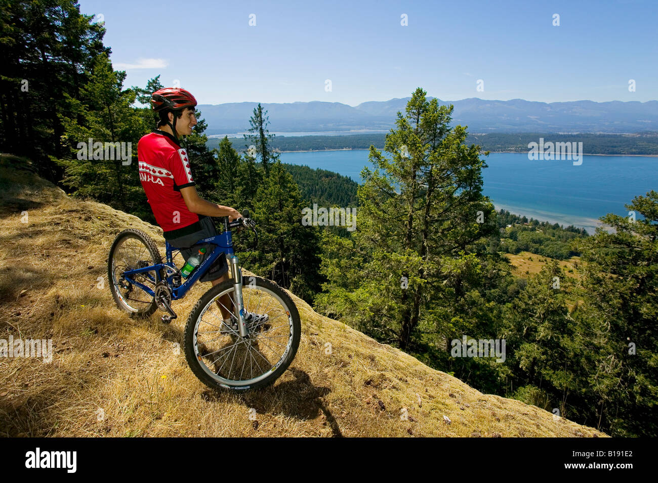 Dylan Holliday on top of Mount Geoffrey on Hornby Island overlooking Baynes sound back towards Vancouver Island. - Stock Image