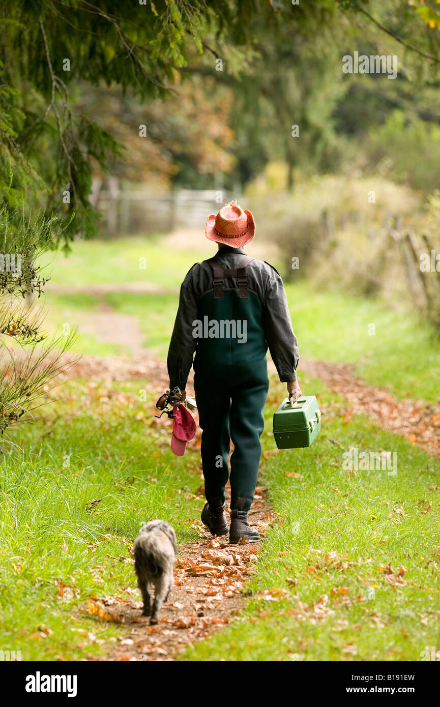 Man and Dog walking home after a day fishing.  Courtenay, Vancouver Island, British Columbia, Canada - Stock Image