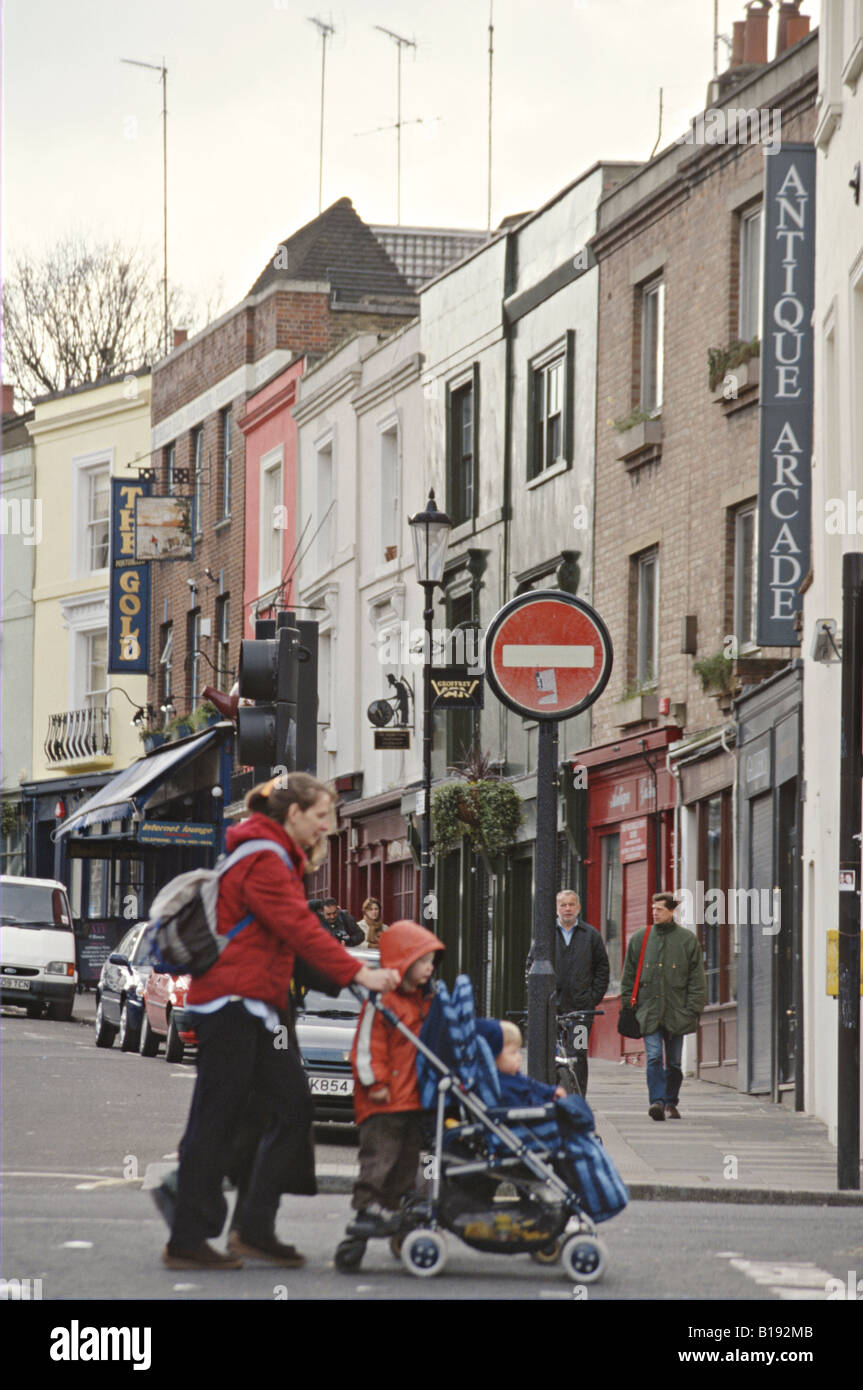 GREAT BRITAIN London Notting Hill antique stores along Portobello road pedestrians woman push stroller with children - Stock Image
