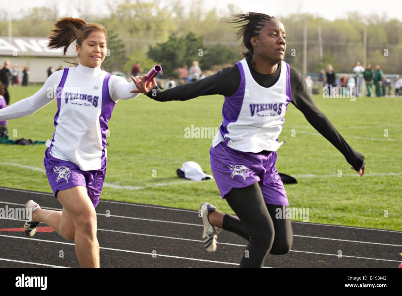 TRACK Glenview Illinois Sprint relay two female runners exchange baton high school girls track meet - Stock Image