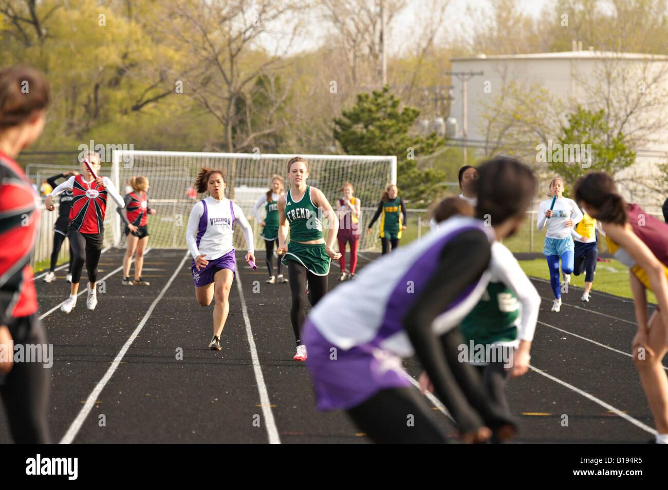 TRACK Glenview Illinois Sprinters await handoff from teammate relay race High school girls track meet - Stock Image