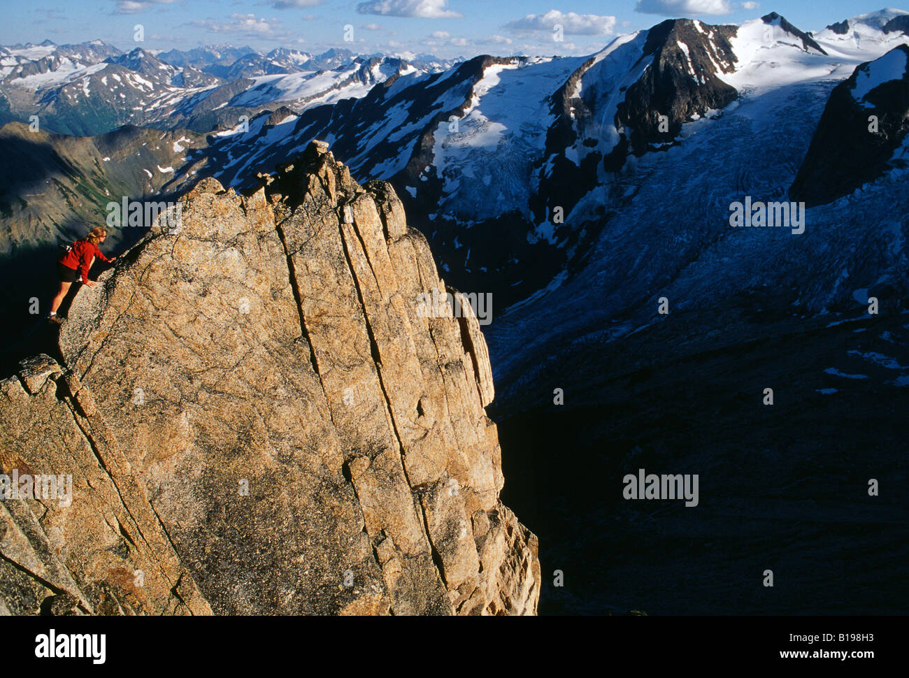 A women on the summit ridge of Eastpost Spire, Bugaboo Provincial Park, British Columbia, Canada. - Stock Image