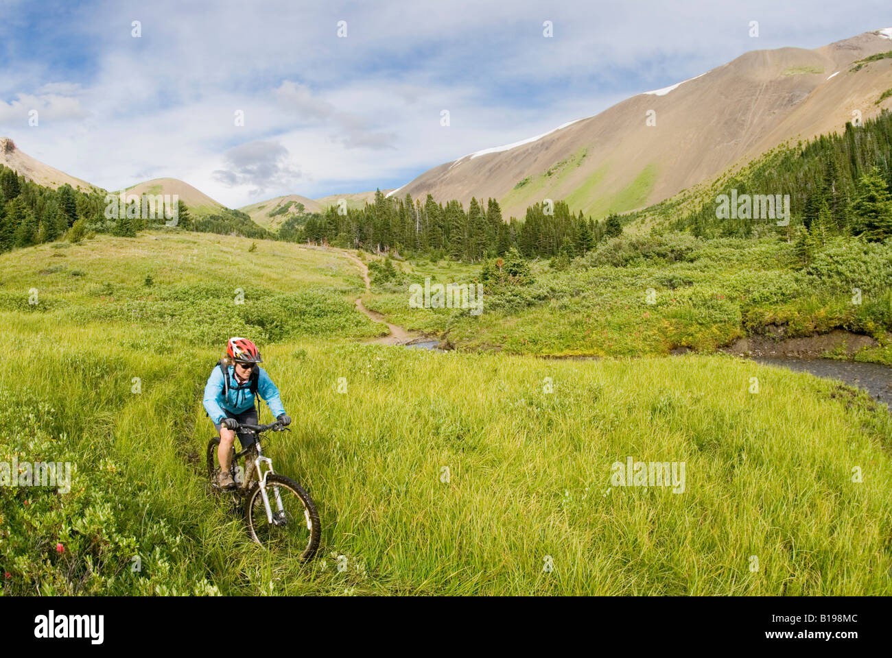 Mountain biker rides down from Windy Pass, Southern Chilcotin Mountains, British Columbia, Canada. Stock Photo