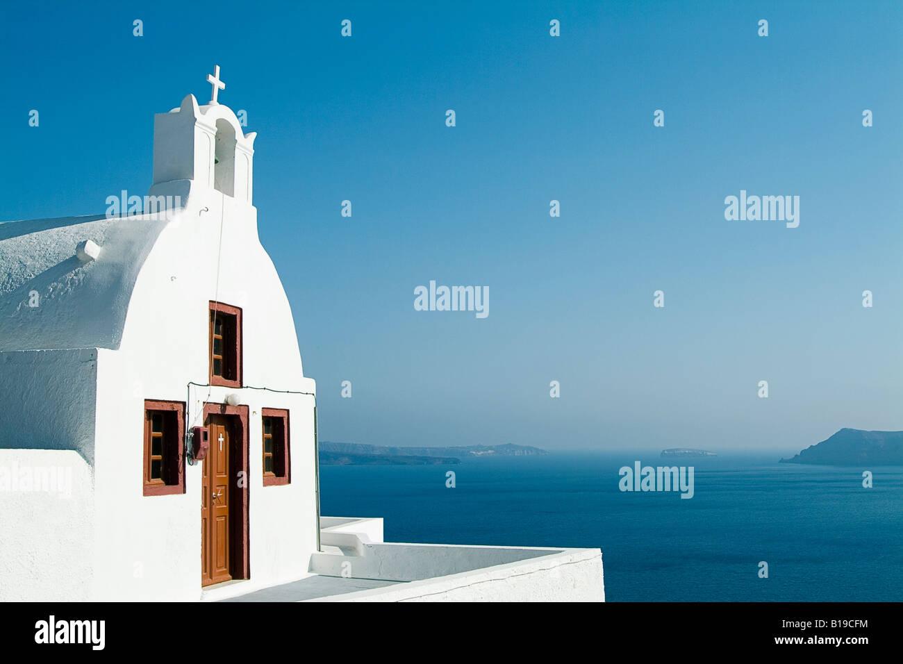 Church overlooking Aegean Sea, Oia, Santorini, Cyclades Islands, Greece. - Stock Image