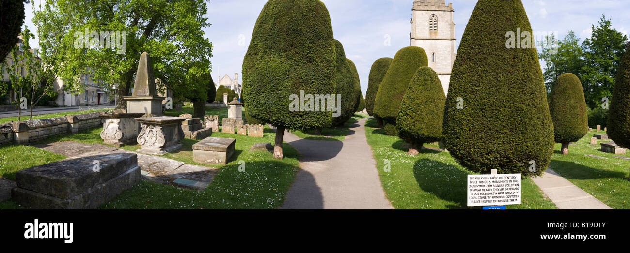 Carved stone tombs and some of the 99 yew trees in the churchyard of the Cotswold village of Painswick, Gloucestershire - Stock Image