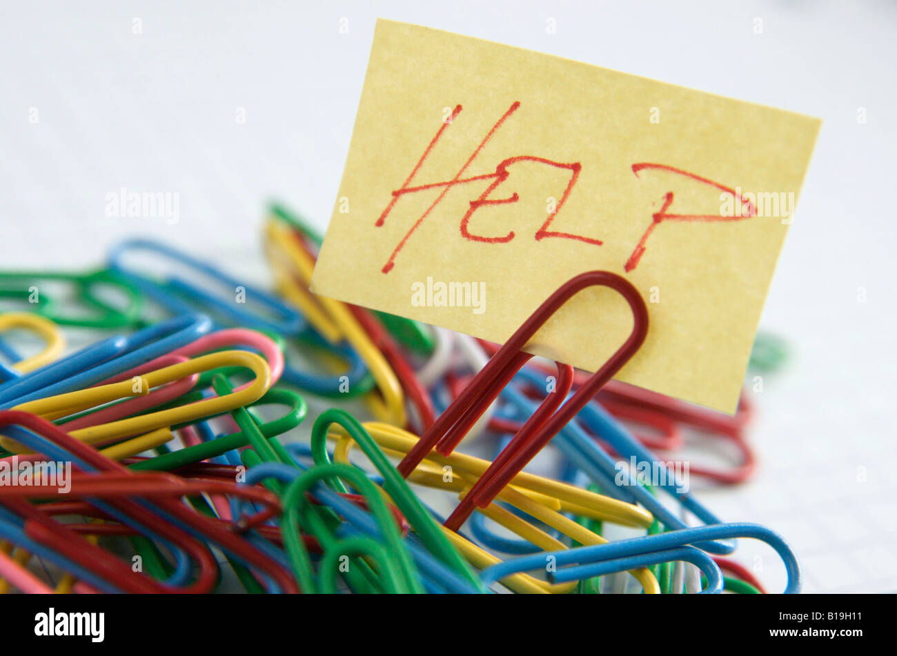 Paper clips and post it note with Help written on it - organisation / office / work concept - Stock Image