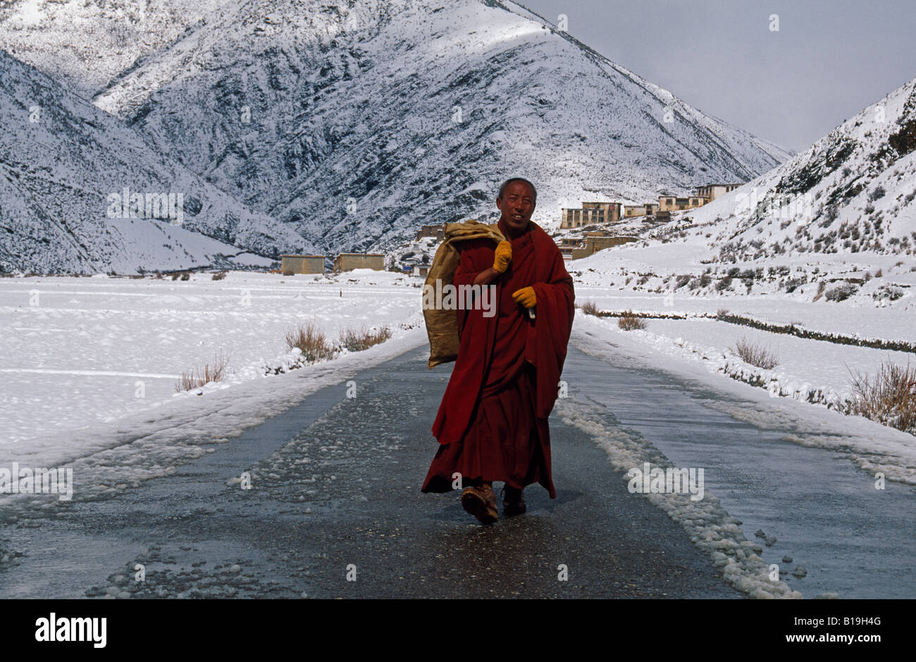 Tibet,  Kham, Pomda. A monk strolls down the road near his local monastery. Sudden storms can block roads well into Stock Photo