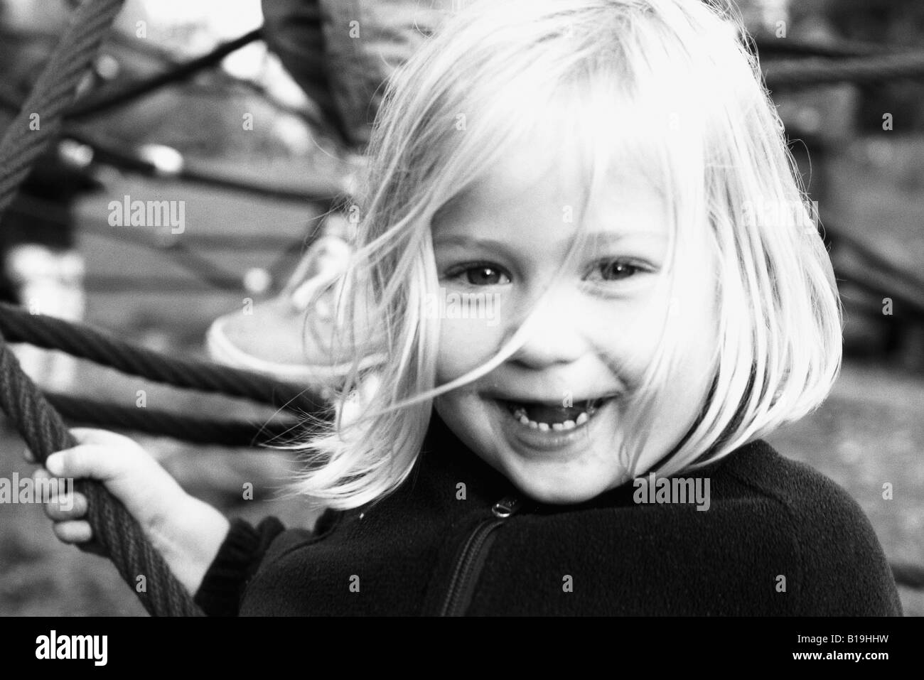 Little girl, smiling at camera, portrait, black and white - Stock Image