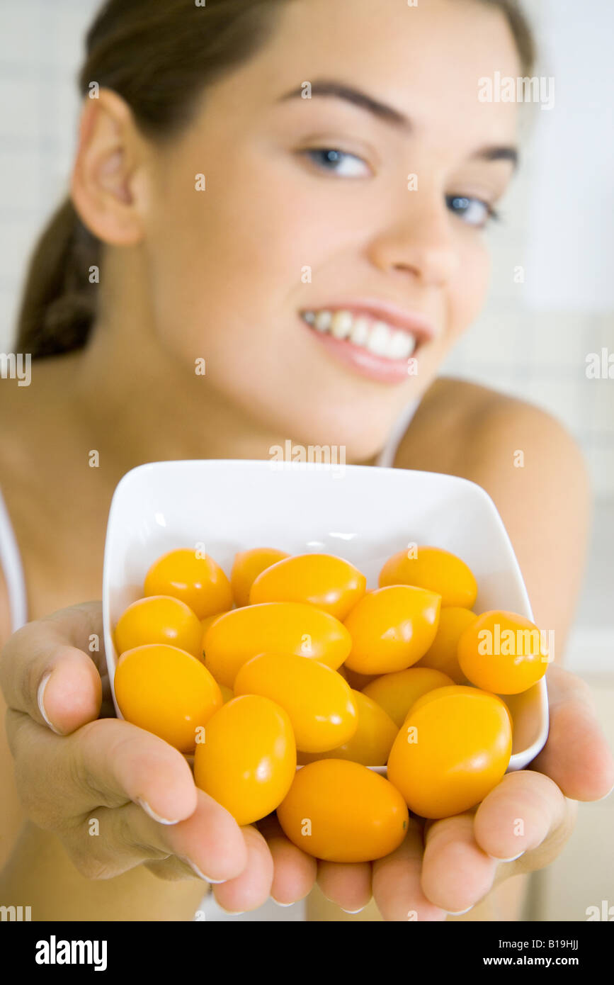 Young woman holding out bowl of yellow cherry tomatoes - Stock Image