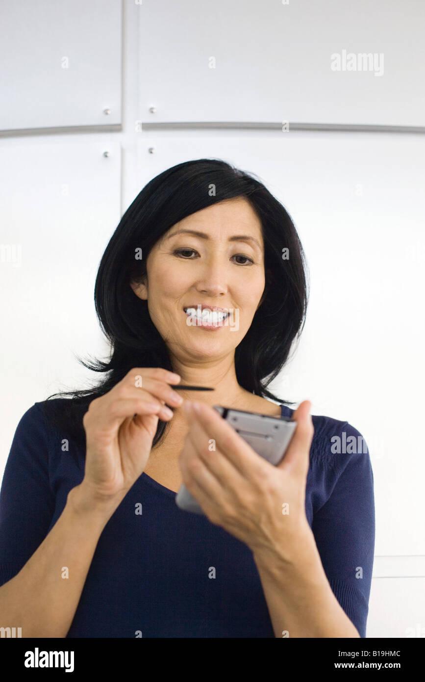Woman using electronic organizer, smiling - Stock Image