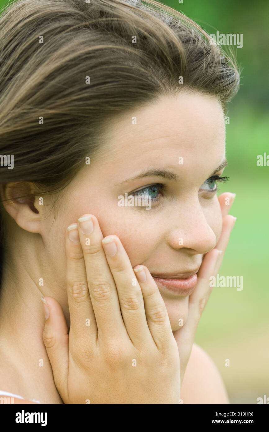 Teen girl holding face in hands, close-up - Stock Image