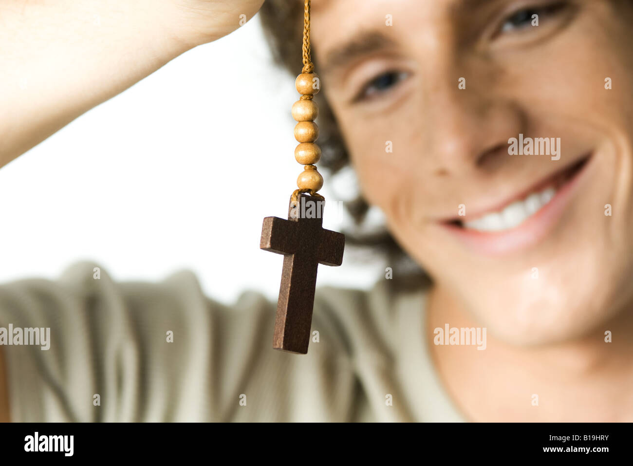 Young man looking at cross, smiling, close-up - Stock Image