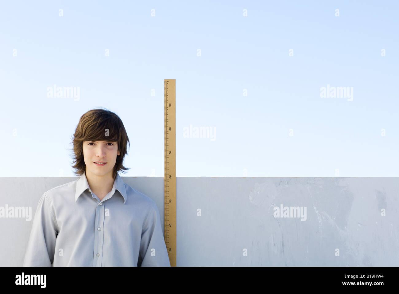 Young man standing beside yardstick, smiling at camera - Stock Image