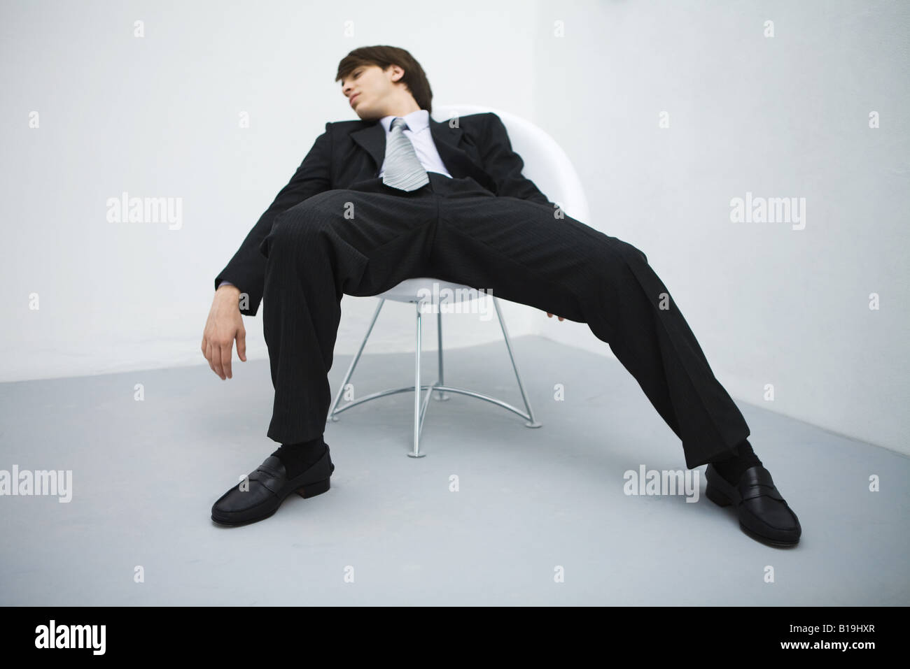 Young Businessman Slouching In Chair Eyes Closed Stock