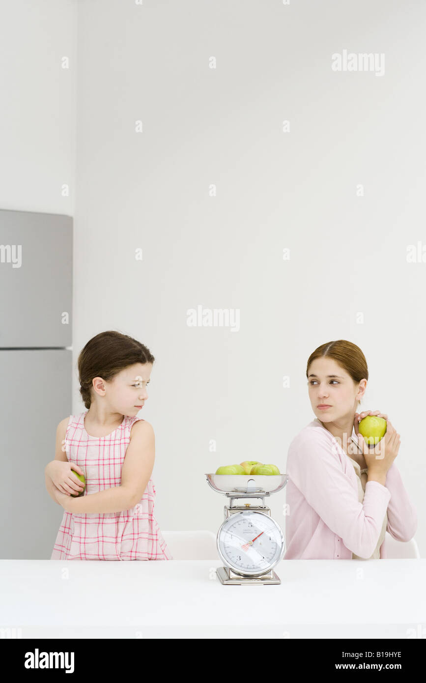 Mother and daughter weighing apples on scale, each holding apple and frowning over shoulder at one another - Stock Image