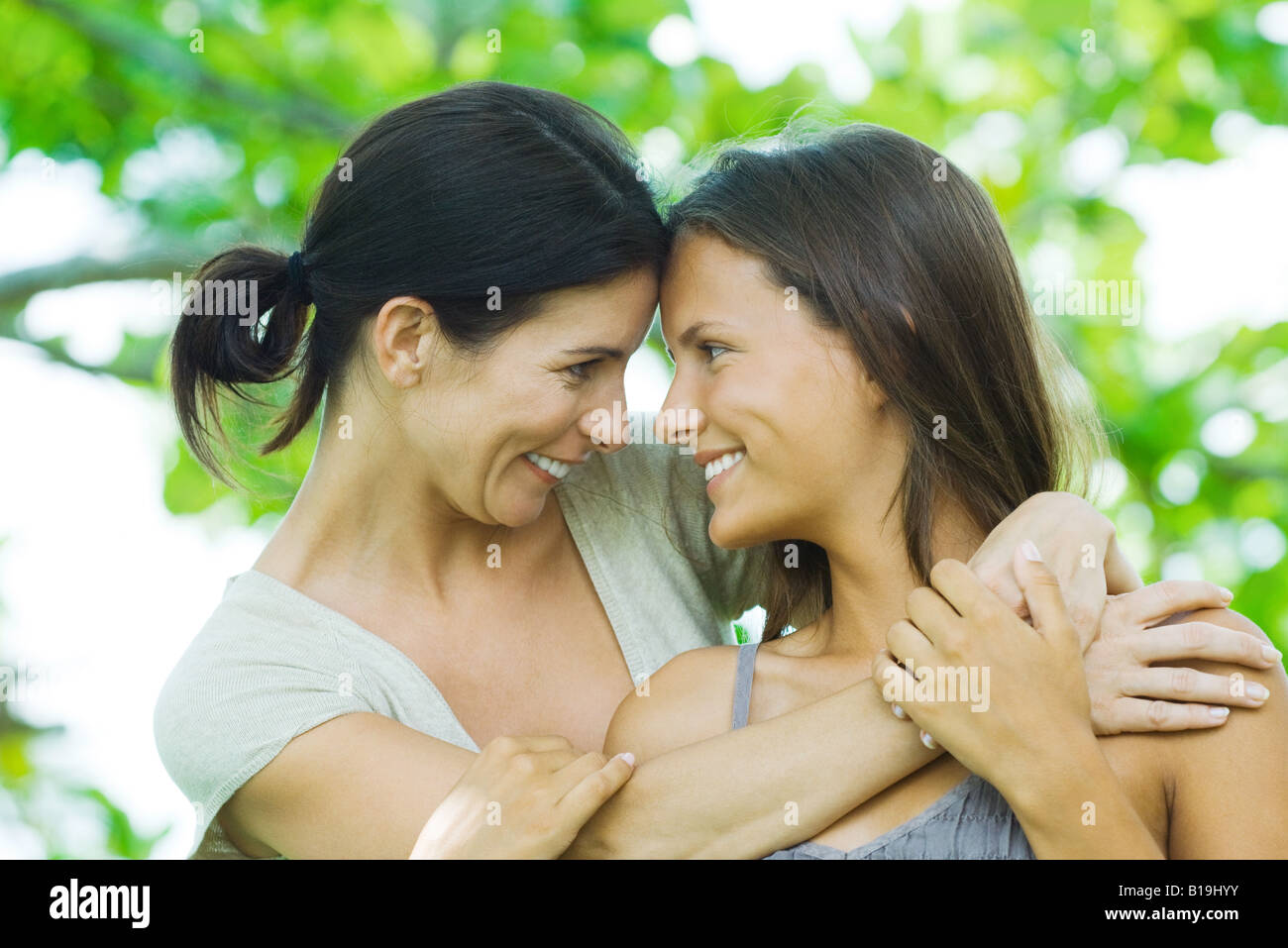 Mother and teen daughter embracing, smiling at each other, touching foreheads - Stock Image