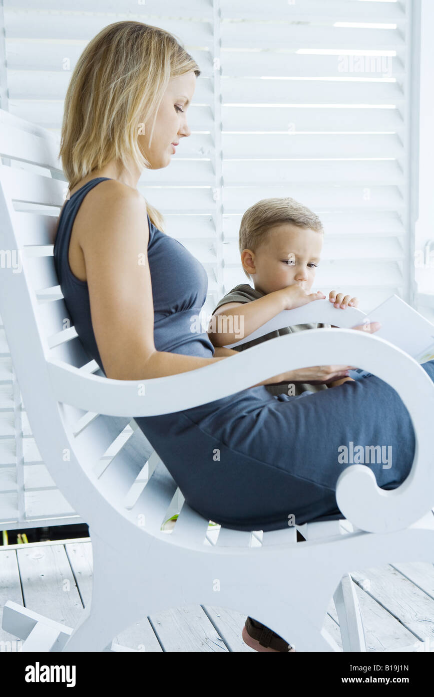 Woman sitting in rocking chair, looking at book with young son - Stock Image