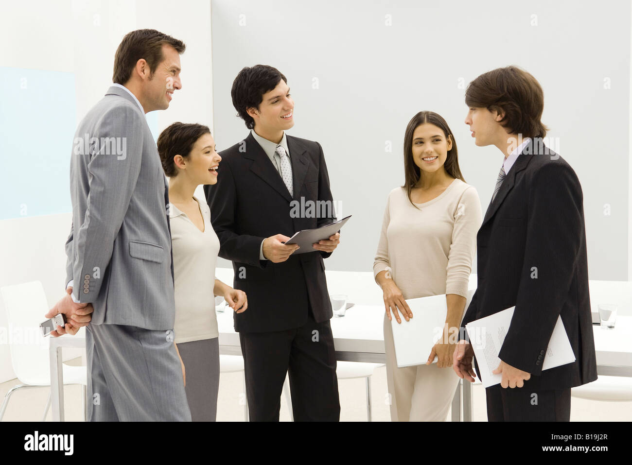 Group of business associates standing together, smiling, chatting - Stock Image