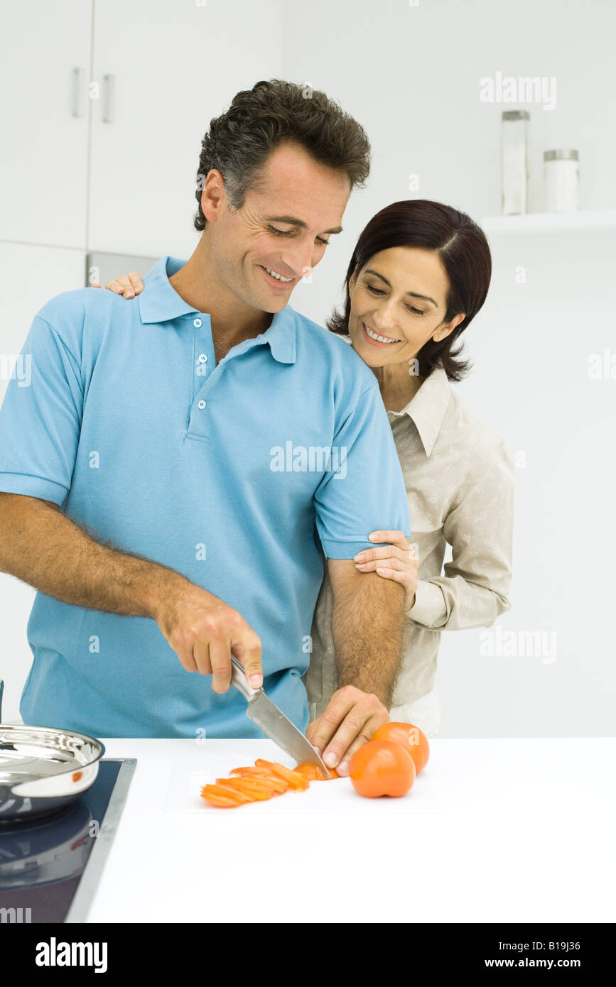 Couple standing together in kitchen, man slicing tomato, both smiling - Stock Image