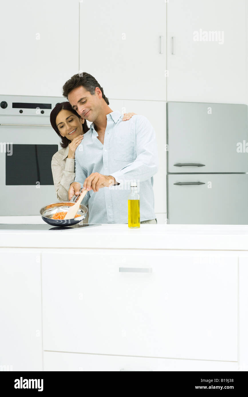 Couple cooking together in kitchen, smiling - Stock Image
